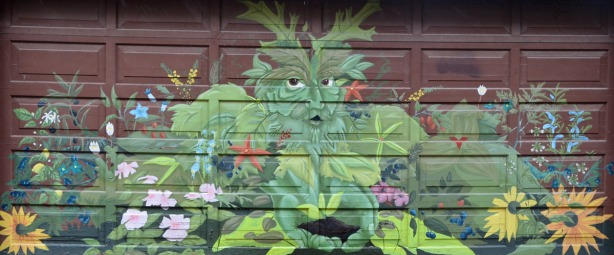 Mural on a garage door showing a man like figure made of leaves and other greenery.  He is surrounded by, of made up of,  flowers and plants