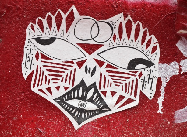 A stencil graffiti of a stylized face in black and white.  It is on a very red wall.