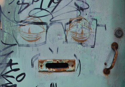 graffiti of a man's face.  The mouth is actually a mail slot in a door.