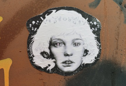 A stencil graffiti of a woman's head. She has shoulder length hair and she is staring straight ahead with a stunned look on her face.