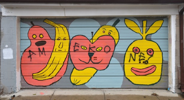 Street art on a garage door showing large stylized fruit with faces on them.  A yellow banana, an orangish pink pear and apple and two other pieces of yellow fruit.