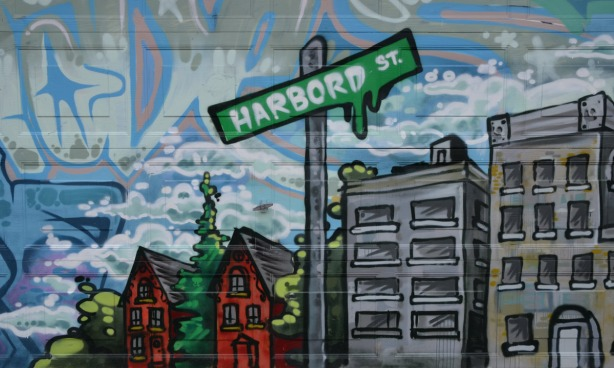 mural showing two red brick houses, a small grey apartment building and a green street sign that says Harbord St.