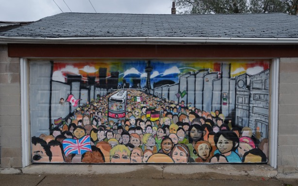 Mural on a garage door showing a large group of people of many different races.  There is a TTC street car in the center of the crowd.  Some people are waving flags - a Canadian flag, a German flag, and a Union Jack