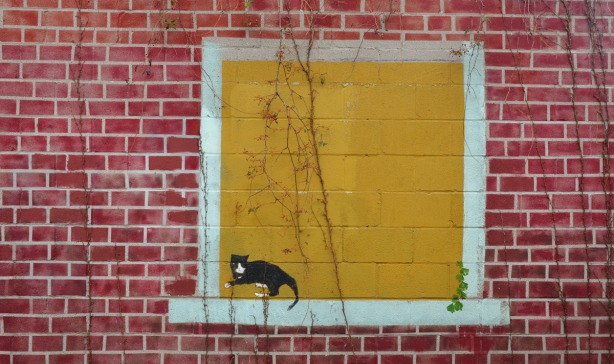 Mural painted on the side of a garage.  It has been painted to look like a red brick wall.  In the wall is a yellow window and a black cat is standing on the window sill.