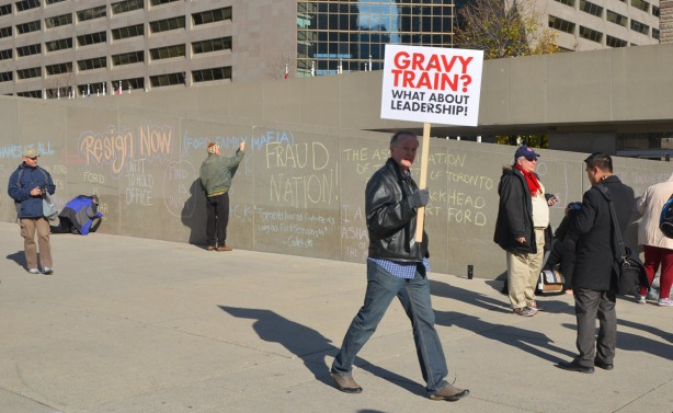 A man is walking past holding up a sign that says Gravy Train? What about Leadership?  In the background people are writing on the wall.