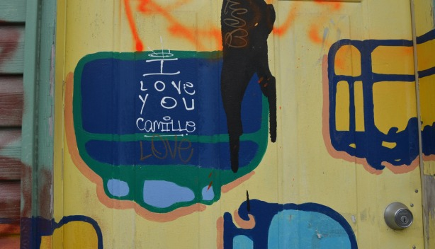 detail of a green and blue blob on a door.  In the blob shape someone has written I love you Camille