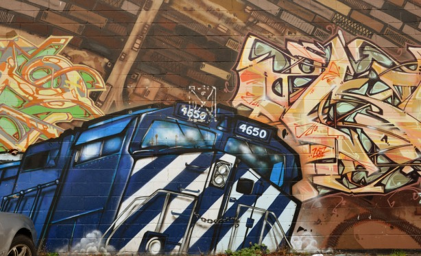 mural of a large blue and white locomotive that is painted to look like it is coming out of a brown brick building