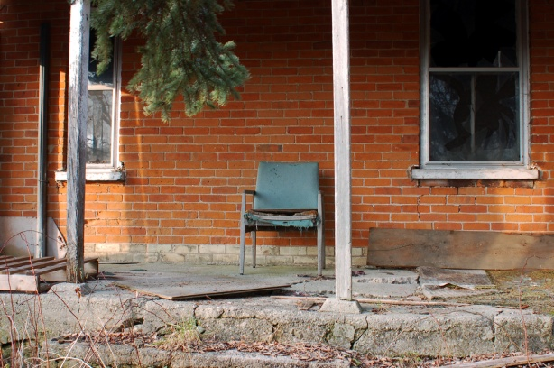 An old blue chair sits on the concrete porch of a house