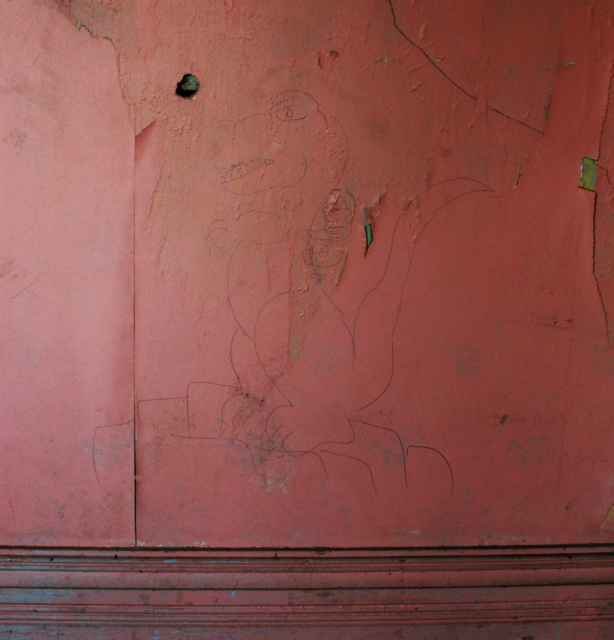 A very pink wall on which someone has drawn a picture of what looks like a dinosaur that is sitting on his hind legs.  On the back of the dinosaur, there is a small boy who is clinging to the dinosaur's neck