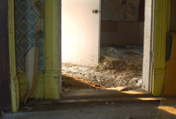 Close up of the lower part of a doorway.  In the foreground are walls covered with blue and white wallpaper.   The wood trim is bright yellow.  The doorway opens into a room whose floor is covered with debris.  In the second room is a door that is open to the outside and lots of sunlight is coming into the room.