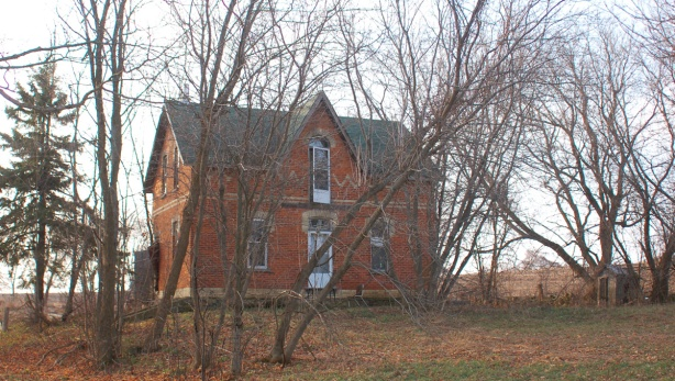 red brick farm house on a small hill.  It is surrounded by trees but because it is November, there are no leaves on the trees.   The house is two storeys tall and has a center gabled roof.