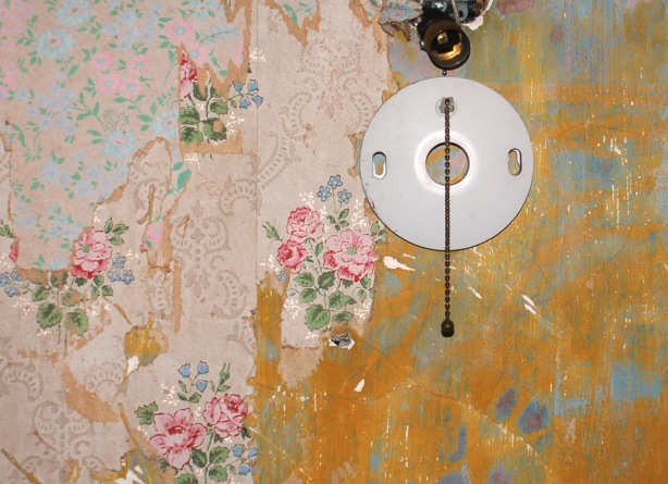 Close up of a wall.  The pink floral wallpaper is peeling off, exposing a yellowish blue layer.  A broken wall light fixture is also in the picture