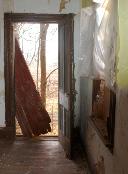A view from inside the house, looking out the door.  A wood external door has come off its hinges and is leaning diagonally across part of the doorway.