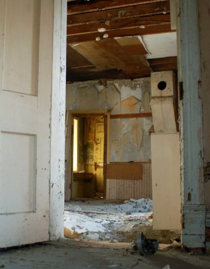 Looking through an open doorway into a room that has a layer of debris on the floor.  The ceiling has fallen (or been removed) and just the wood can be seen.