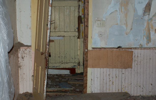 A view of a wall that has pink wainscotting.  The wallpaper on the top part of the wall is peeling off.  In the wall is a door to the next room.  The door is open.