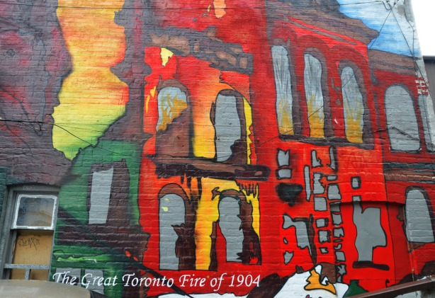 a very bright and colourful mural on the back of a brick building,  It shows, in reds, yellows ans oranges the burning of a couple of brick buildings, with flames coming out of the windows.