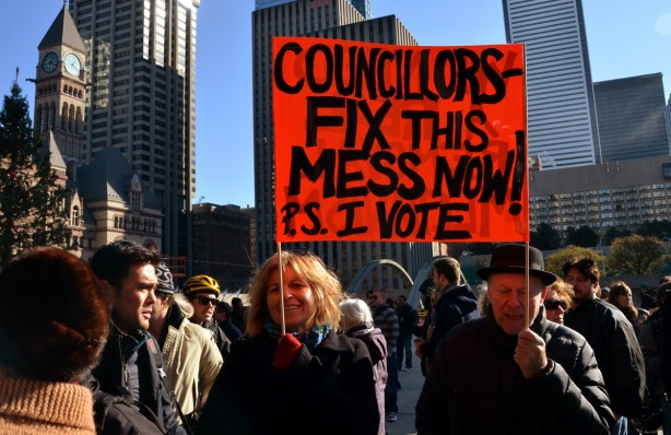 A couple is holding an orange sign that says Councillors fix this mess now.  P.S. I vote.