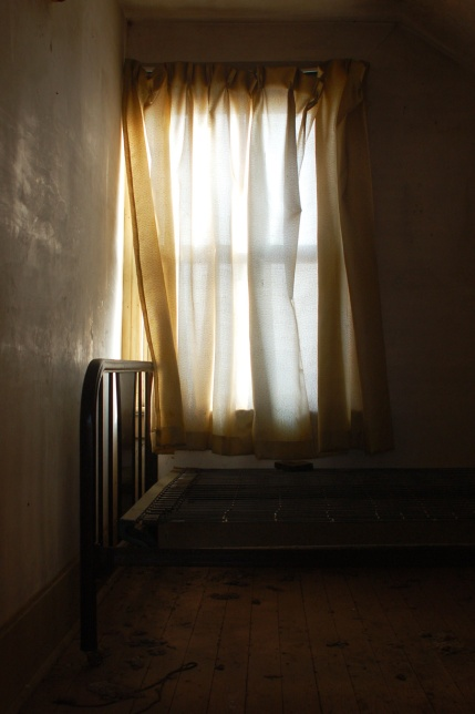 A bedroom where the only thing in the room is an old bed frame and springs.  The bed is in front of a window that has an old gold coloured curtain on it.  Sunlight is coming through the window and lighting up that area of the bedroom.