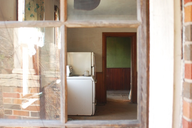 Two small window panes in a door are broken, there is no glass.  When you look through the window you see into the kitchen where there is a stove and a fridge. Otherwise, the house is abandoned.