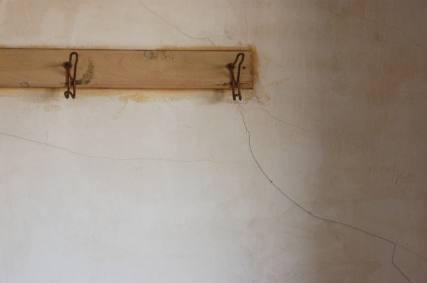 two old rusted hooks on a board that is nailed to a wall.  The wall is grey colour.  There is a crack that runs diagonally across the wall.
