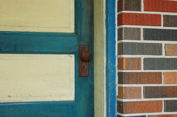 close up view of a door that is painted yellow and blue.  The door frame is also yellow and blue.  The door knob is rusted.  Some of the brick of the house is also in the photo