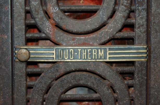 Close up of the door of an old oil stove showing the ironwork and a metal logo.  The logo on the door says Duo-Therm.