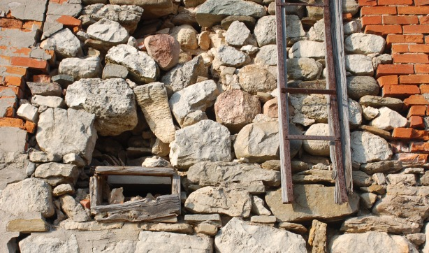 A wall that is part stone and part brick.  In the stonework is a small wood window frame (no glass).  A ladder leans against the wall but it doesn't touch the ground.