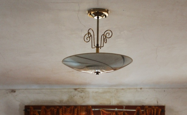 old brass ceiling lamp is hanging from a grubby ceililng.  There is a crack in the ceiling.