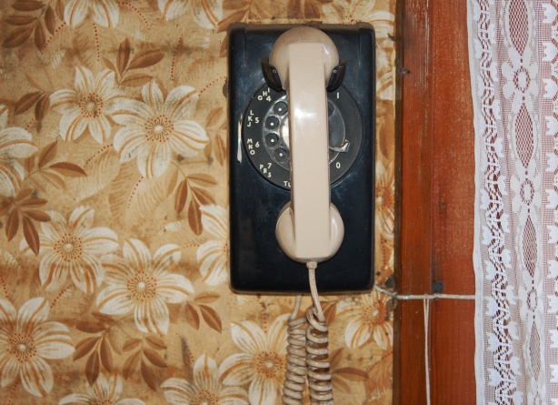 an old rectangular rotary phone hangs on a wall that is covered with brown, beige and white floral wallpaper.  The phone is black but has a beige handset.