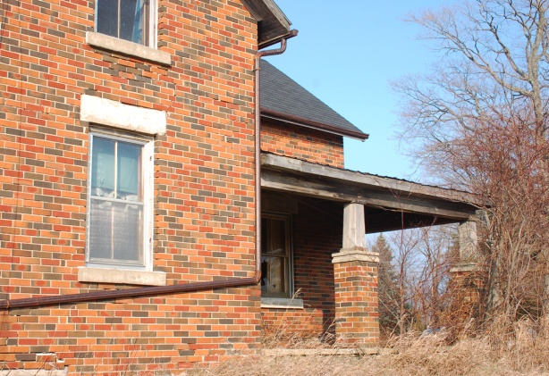side view of a brick farm house showing the porch and a couple of windows.