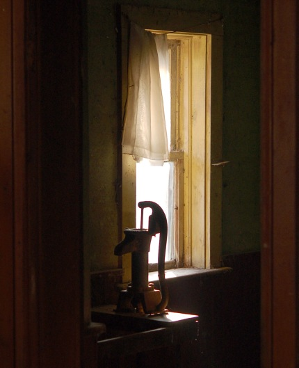 On a counter there is an old hand pump (or water).  It is backlit by sunlight coming through a window.  There is part of an old sheer curtain covering the top part of the window