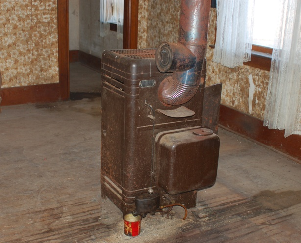 in the middle of living room there is an old oil burning stove.  It is near the middle of the room.