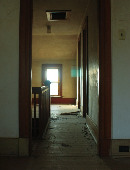looking down a hallway towards a window.  There is a bannister on the left and a couple of doorways on the right.  The floor is dirty.