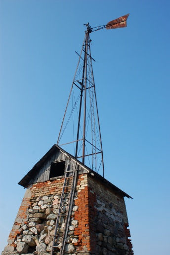 The windmill.  Stone and brick building, pump house, below with a metal frame teepee shaped structure on top.