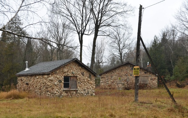 Two small buildings made of field stones.