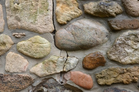 close up of a wall made of field stones.  There is a vertical crack running down the wall.