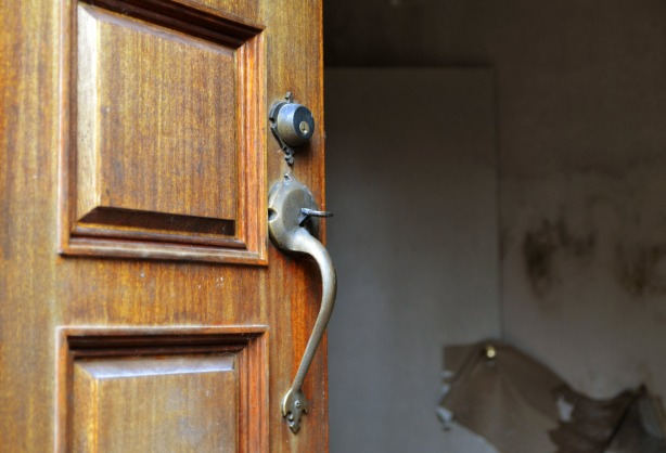 close up of a wood door showing the middle section of the door with a metal lock and handle.  The interior of the house is barely visible but it looks grey inside.