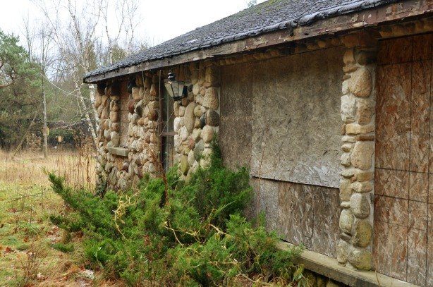 One side of a stone building.  The windows are covered with plywood.  There is a large juniper bush growing in front of the house.