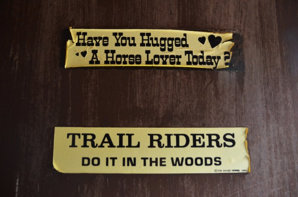two yellow bumper stickers on a wood door.  The bottom one says Trail Riders Do It in the Woods.   The top one says Have You Hugged a Horse Lover Today?