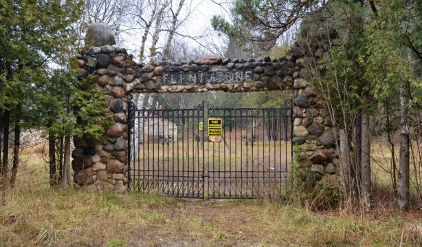 locked metal gate with a stone column on each side.  Across the top is a sign, also made of stones, that says Flintstone