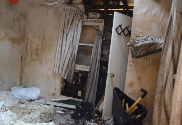inside of a very dirty abandoned building.  Grey curtains are falling down, there is lots of debris on the floor,  and there is lots of dirt and mold on the grey walls.