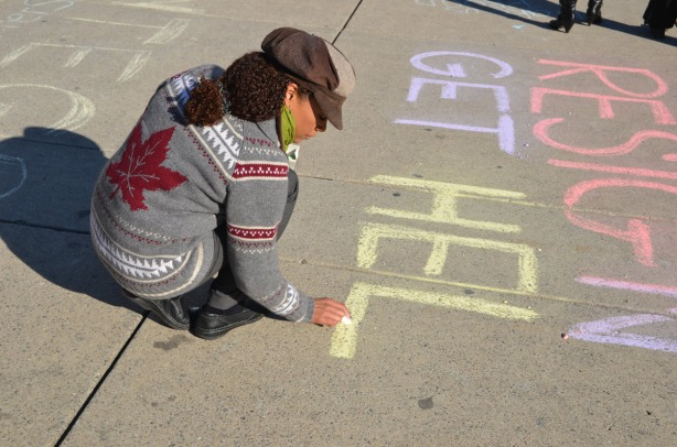 A woman is writing Get Help in purple and yellow chalk, on the ground