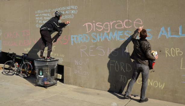 Two people are writing words in chalk on a concrete wall.  A woman is standing on a garbage bin so that she can reach higher up on the wall.
