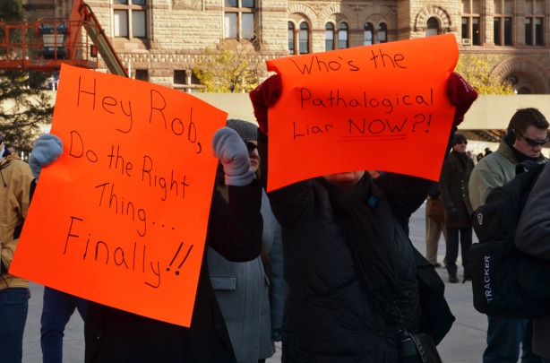 Two woman are holding bright orange signs.