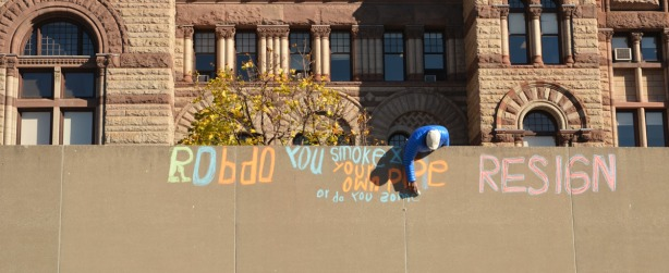 A man is writing in orange and blue chalk.  Old City Hall is in the background.
