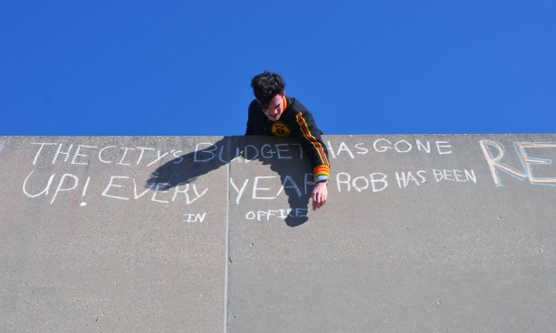 A man is writing with chalk on a grey concrete wall.