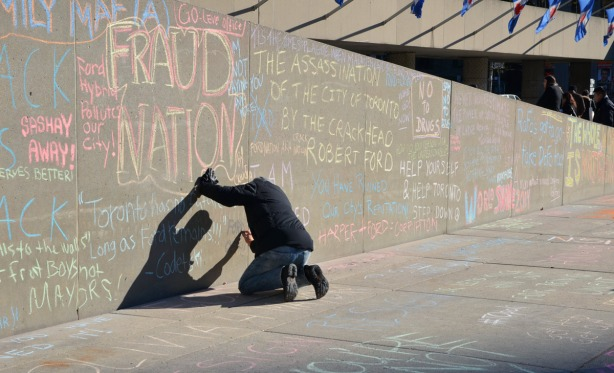 A man is writing words on the concrete wall beside the ramp at Nathan Phillips Square.