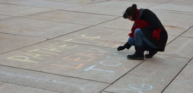 A woman is writing Pathetic Leave Toronto in coloured chalk on the concrete ground in the middle of the square.