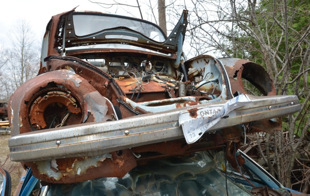 An old Volkswagen Beetle sits on the roof of another car.  Not much except the frame remains of the Bug.