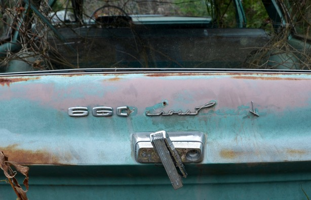 The back end of a rusty, once light blue,  660 Cross Country model of car